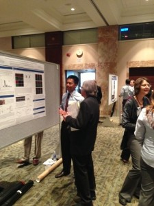 Ron Menorca, CTSI Year Out trainee, explains his poster to Dr. Anthony Windebank, TL1 Program Director for the Mayo Clinic Center